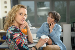 坐在桌上的两名妇女在厨房和饮用的咖啡里 库存图片