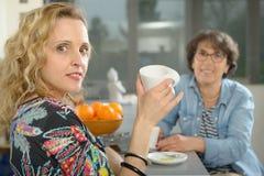 坐在桌上的两名妇女在厨房和饮用的咖啡里 库存照片