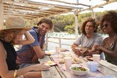 坐在桌上的两对夫妇在海边,伊维萨岛,西班牙 免版税库存照片