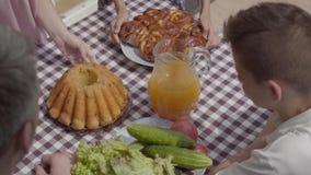 坐在桌上的人和男孩,吃午餐在享受一好日子的庭院里 妇女和带来酥皮点心的女孩 股票视频