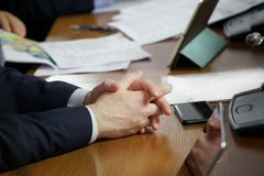 坐在桌上的人的手在业务会议期间 免版税库存照片