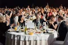坐在桌上的人们在仪式奖励期间 库存图片