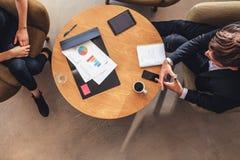 坐在桌上的企业同事在合作会议期间 免版税库存图片