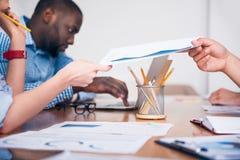 坐在桌上的包含的宜人的同事 免版税库存图片