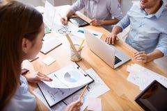 坐在桌上的包含的繁忙的同事 免版税库存图片