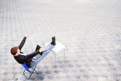 坐在桌上的商人外面 免版税库存照片