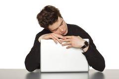 坐在桌上的商人,睡觉拥抱膝上型计算机 免版税库存图片