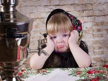 坐在桌上的女孩哀伤 免版税库存照片