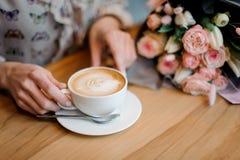 坐在桌上的女孩拿着一杯咖啡在美丽的花束附近 免版税库存照片