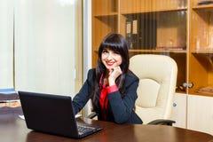 坐在桌上的好女实业家在办公室 图库摄影