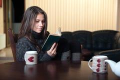 坐在桌上的妇女读有趣的书 库存照片