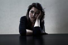 坐在桌上的孤独的哀伤的女孩 免版税库存照片