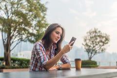 坐在桌上的少妇户外使用她的手机 在智能手机的女性读书正文消息在公园 免版税库存照片