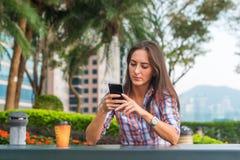 坐在桌上的少妇户外使用她的手机 在智能手机的女性读书正文消息在公园 库存图片