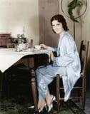 坐在桌上的少妇食用早餐茶(所有人被描述不更长生存,并且庄园不存在 供应商wa 免版税库存照片
