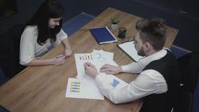 坐在桌上的年轻人和妇女在办公室 分析,谈论和画在图的同事和 股票视频