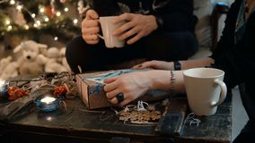 坐在桌上的年轻夫妇特写镜头视图,在圣诞树附近和打开当前假日,饮用的茶 影视素材