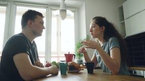 坐在桌上的年轻白种人夫妇在dicussing某事用正面方式的现代lighty宽敞厨房,他们是 股票录像