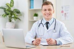 坐在桌上的微笑的儿科医生 库存照片