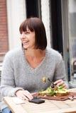 坐在桌上的微笑的妇女吃食物 图库摄影