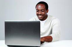 坐在桌上的愉快的非洲人 免版税库存照片