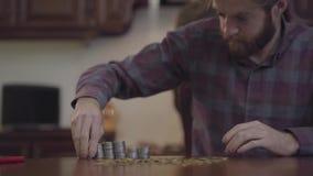 坐在桌上的有胡子的人画象在计数金钱的厨房里 在方格的衬衣堆银的Beardie 股票录像