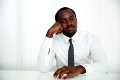 坐在桌上的沉思非洲人 图库摄影