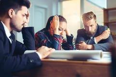 坐在桌上的沮丧的商人在办公室,争论,当谈论项目时 库存照片