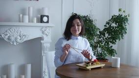 坐在桌上的深色的女孩在日本餐馆 由筷子吃寿司 正餐 影视素材
