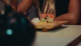 坐在桌上的深色的女孩在日本餐馆 由筷子吃寿司 影视素材