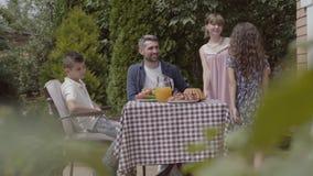 坐在桌上的爸爸、妈妈和他们的两个孩子,吃午餐在庭院里享受一好日子 妇女和女孩 股票录像