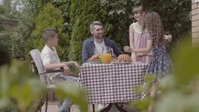 坐在桌上的爸爸、妈妈和他们的两个孩子,吃午餐在庭院里享受一好日子 妇女和女孩 股票视频