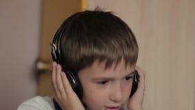 坐在桌上的男孩听到音乐和 股票视频