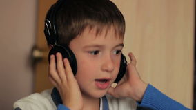 坐在桌上的男孩听到音乐和 股票录像