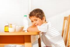 坐在桌上的男孩在早餐期间在厨房里 图库摄影