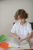 坐在桌上的男小学生和做他的家庭作业 免版税库存图片