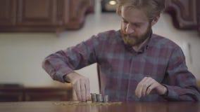 坐在桌上的画象英俊的有胡子的人在计数金钱的厨房里 在方格的衬衣堆的Beardie 影视素材