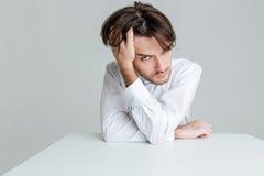 坐在桌上的白色衬衣的沉思人 免版税库存图片