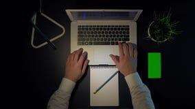 坐在桌上的白色衬衫工作的人使用膝上型计算机和电话 股票视频