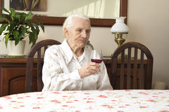 坐在桌上的祖母拿着一杯红葡萄酒 免版税库存照片