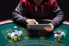 坐在桌上的网上打牌者 免版税库存图片