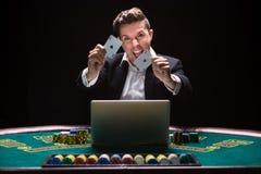 坐在桌上的网上打牌者 库存图片
