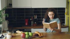 坐在桌上的美丽的卷曲妇女拿着咖啡,在家喝和阅读书在好的厨房里,她是 股票视频