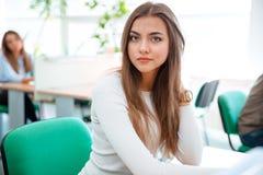 坐在桌上的美丽的女学生 免版税库存照片