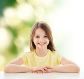 坐在桌上的美丽的小女孩 免版税库存照片