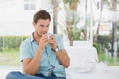 坐在桌上的英俊的人食用咖啡 库存照片