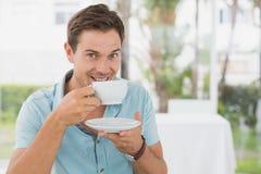 坐在桌上的英俊的人食用咖啡 库存图片