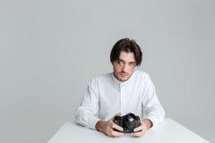 坐在桌上的英俊的年轻深色的人拿着照相机 免版税库存照片