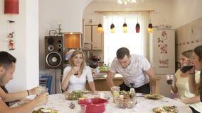 坐在桌上的被会集的愉快的朋友在欢呼的厨房敬酒和享受时间在家一起集会与快餐 股票录像