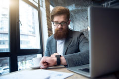 坐在桌上的被集中的有胡子的人 免版税库存图片